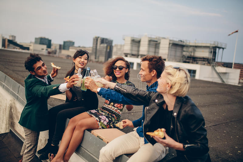 Diverse group of young friends on terrace party. Young men and women having drinks on rooftop party stock photos