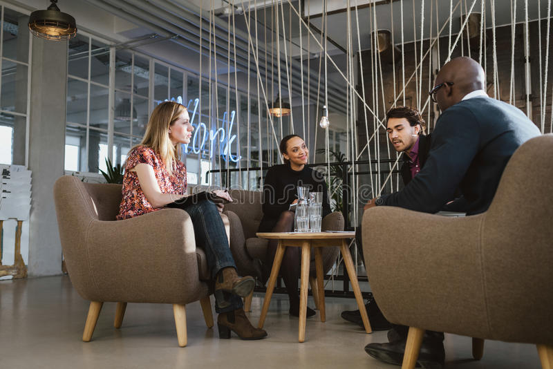 Diverse group of young people having a meeting in lobby royalty free stock images