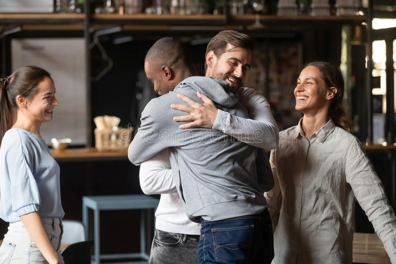 Diverse guys best friends hugging greeting each other at meeting stock image