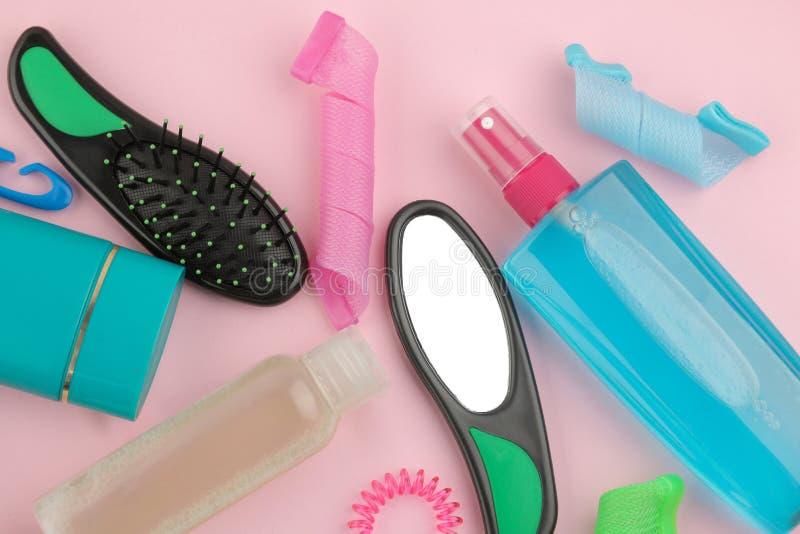 Diverse haarverzorgingproducten en haartoebehoren op een heldere roze achtergrond Haarschoonheidsmiddelen Hoogste mening met plaa royalty-vrije stock foto's