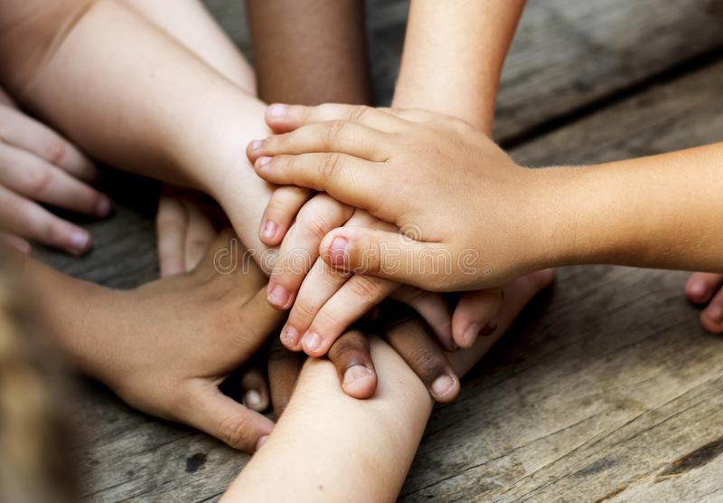 Diverse hands are join together on the wooden table stock photography