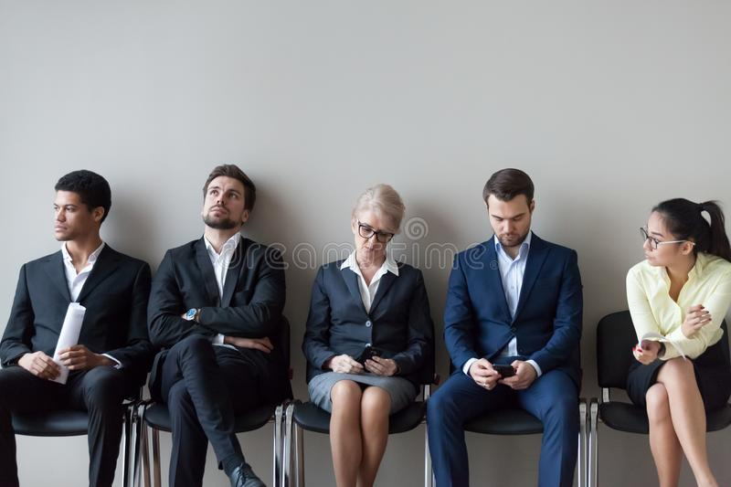 Diverse job candidates sitting waiting in queue for interview stock image