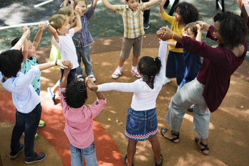 Diverse kindergarten kids arms raised stock photography