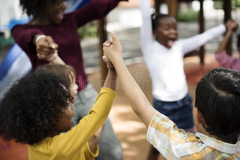 Diverse kindergarten students hands up together royalty free stock photo