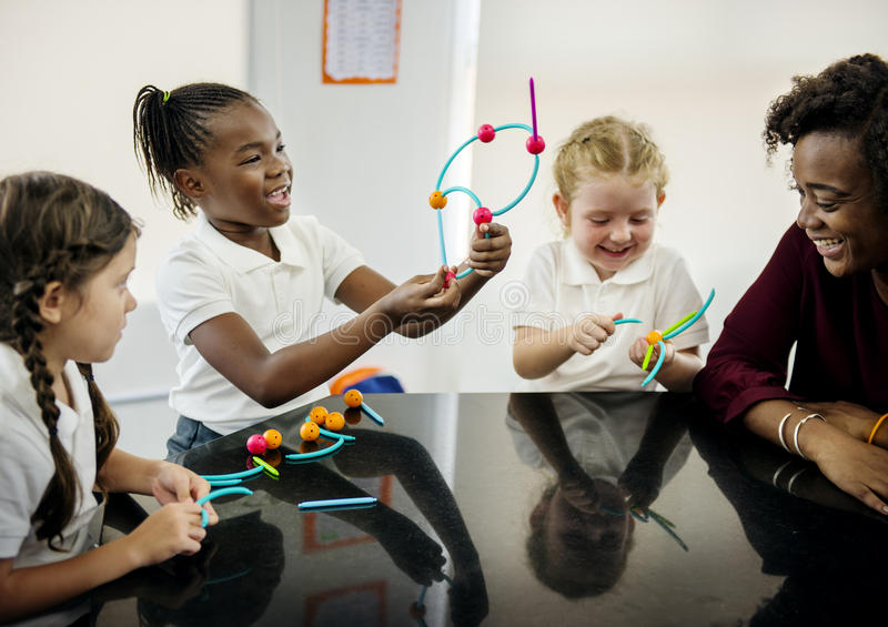 Diverse kindergarten students holding learning structures from t stock photography