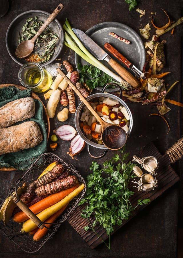 Diverse kleurrijke organische groenteningrediënten van lokale markt op donkere rustieke keuken dienen achtergrond met pot, lepel, stock afbeeldingen