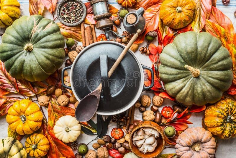 Diverse kleurrijke organische pompoenen en kokende pot met lepel op keukenlijst met noten, kruiden en de herfstbladeren, hoogste  royalty-vrije stock foto