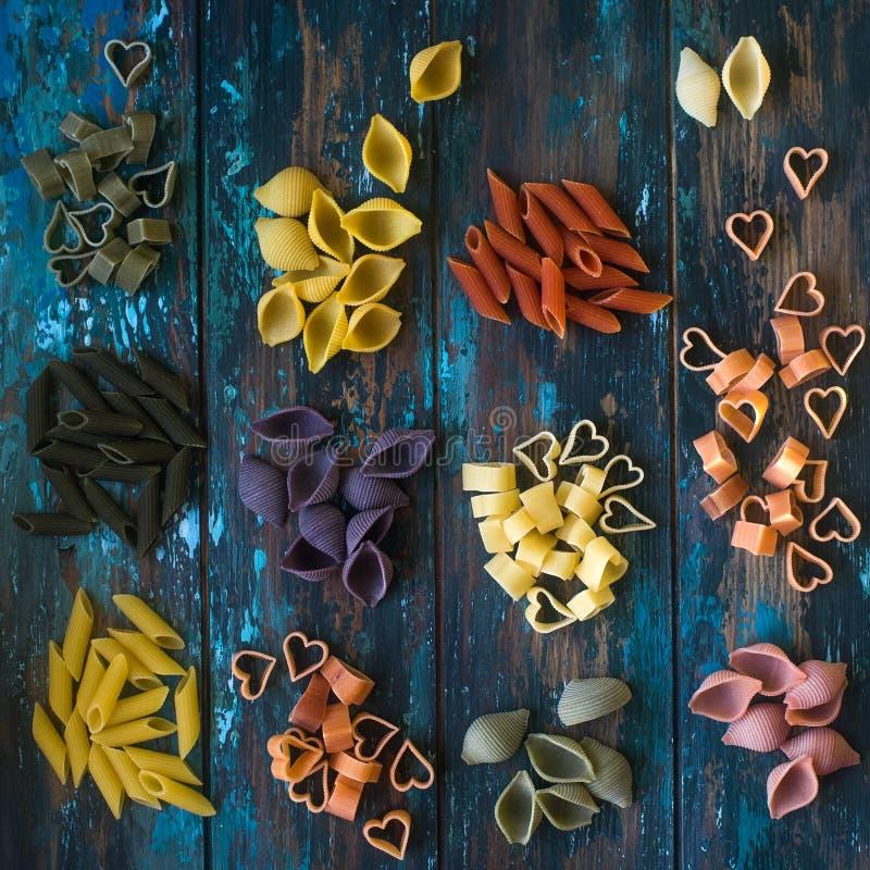 Diverse kleurrijke ruwe deegwaren op rustieke houten lijst royalty-vrije stock afbeelding