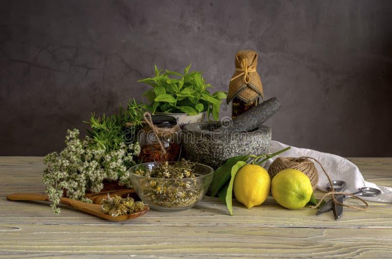 Diverse kruiden en kruiden, citroenen en olijfolie op een houten lijst stock fotografie