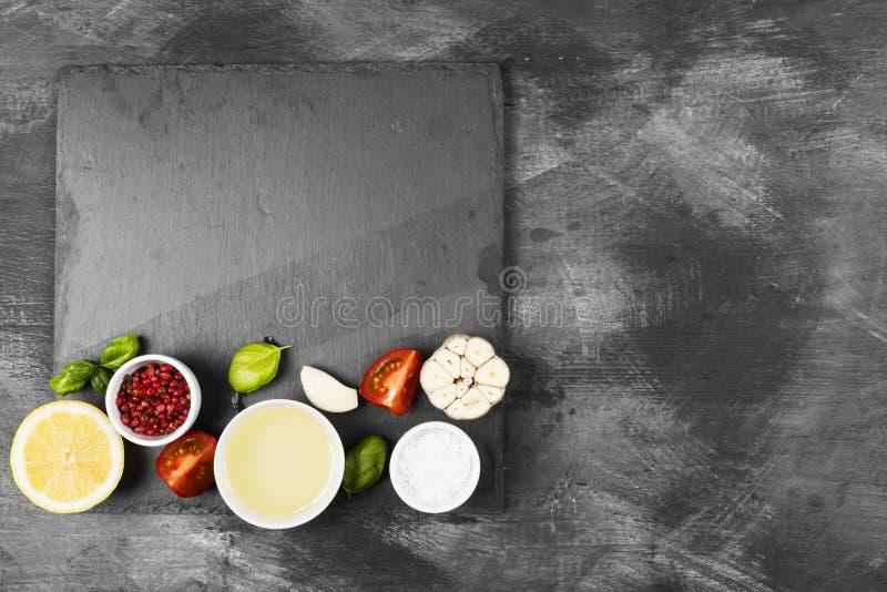 Diverse kruiden, kruiden en groenten op donkere achtergrond de bovenkant wedijvert stock fotografie