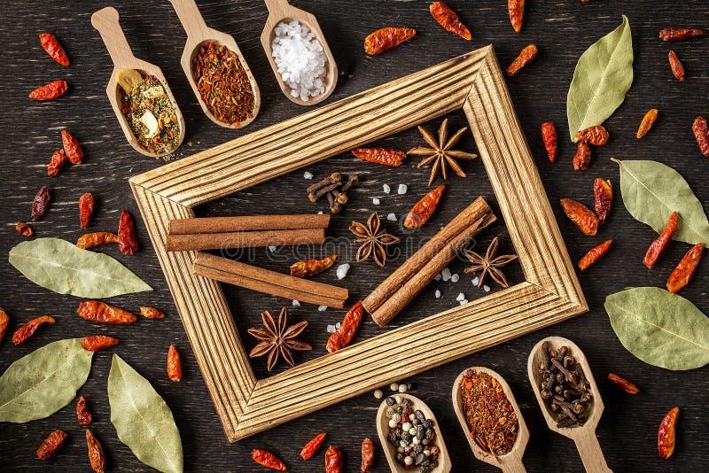 Diverse kruiden in houten lepels op donkere steenlijst royalty-vrije stock afbeeldingen