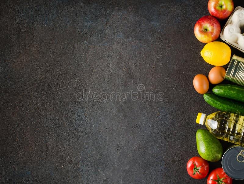 Diverse kruidenierswaren op de achtergrond van donkerbeton Voedselleveringsconcept Voedseldonaties stock foto
