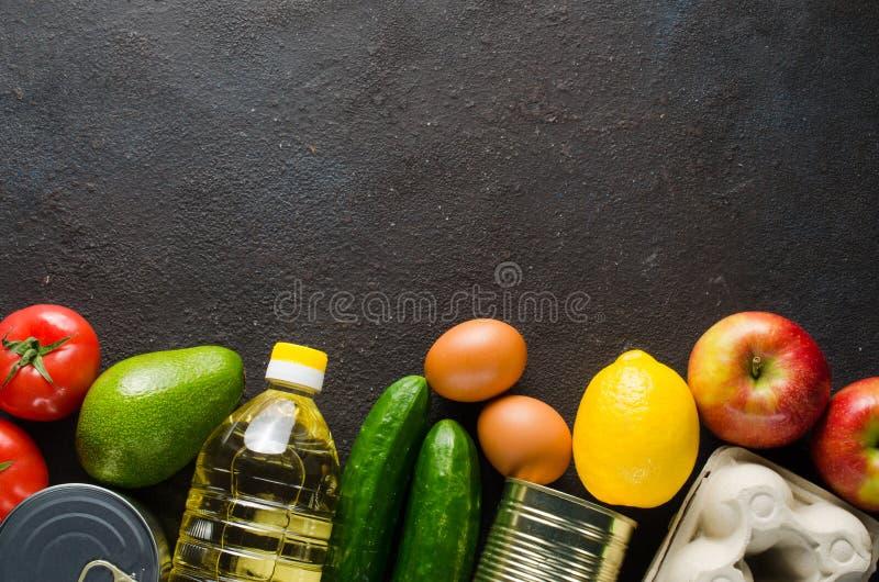 Diverse kruidenierswaren op de achtergrond van donkerbeton Voedselleveringsconcept Voedseldonaties royalty-vrije stock afbeeldingen