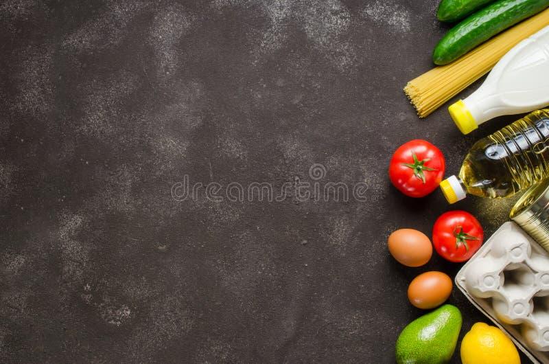 Diverse kruidenierswaren op de achtergrond van donkerbeton Voedselleveringsconcept Voedseldonaties stock fotografie