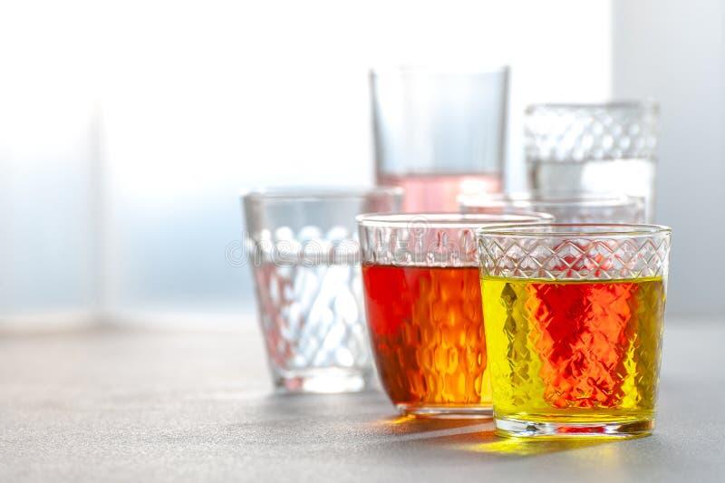 Diverse limonades in glas gefacetteerde glazen op een grijze lijst royalty-vrije stock fotografie