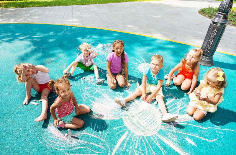Diverse looking kids draw with chalk stock photography