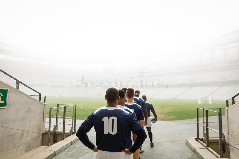 Diverse male rugby players standing at the entrance of stadium in a row for match royalty free stock image