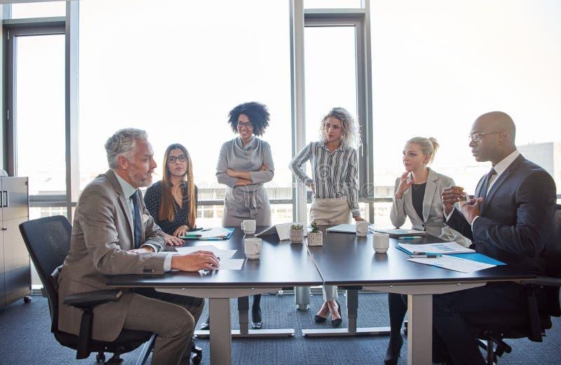 Diverse medewerkers die samen in een bestuurskamer in een bureau samenkomen royalty-vrije stock afbeeldingen