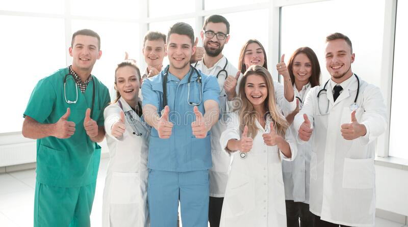 Diverse medical professionals giving a thumbs up stock image
