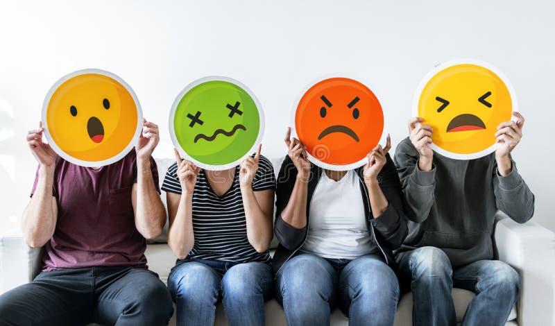 Diverse mensen die emoticon pictogrammen houden stock afbeeldingen