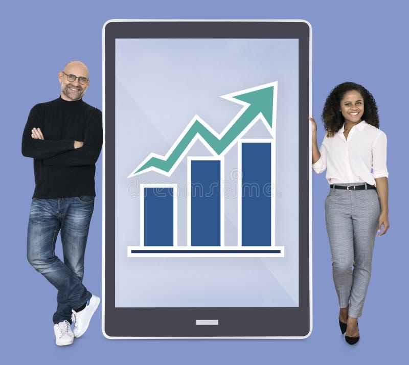 Diverse mensen die grafiek op een tablet tonen royalty-vrije stock afbeeldingen