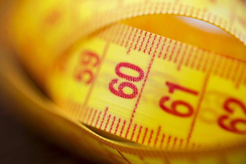 Diverse mesure de bande comme fond Une bande de mesure jaune comme fond Bande de mesure de couleur jaune pour la mesure du lengt photographie stock