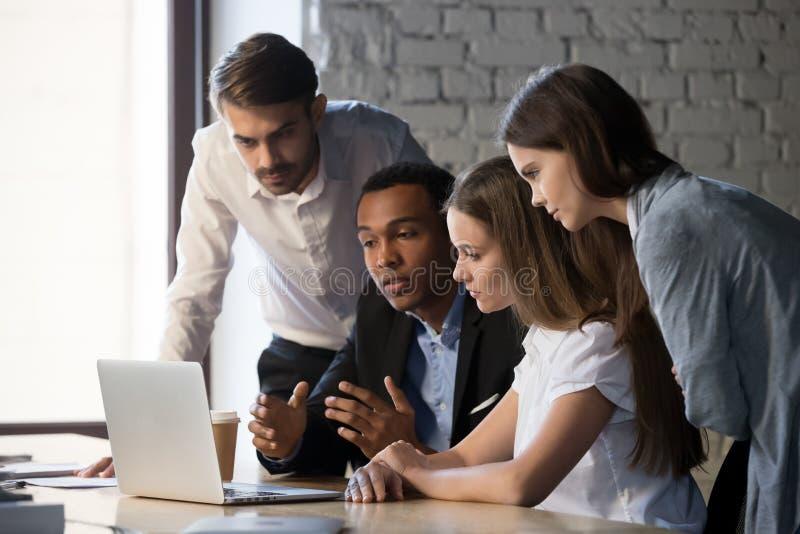 Diverse millennial arbeiders die bij laptop samen samenwerken stock afbeeldingen