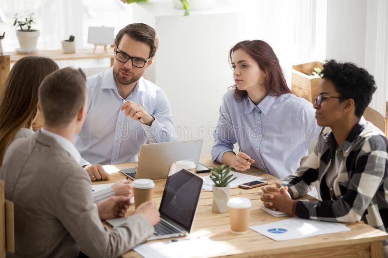 Diverse millennial employees cooperating at office meeting royalty free stock photos