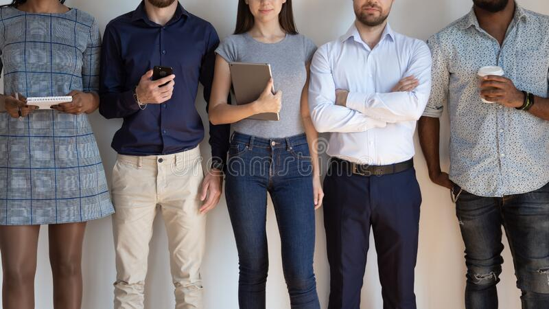 Diverse millennial people stand in row at office together. Crop close up of diverse millennial company professionals HR team stand in row at white wall together stock photography