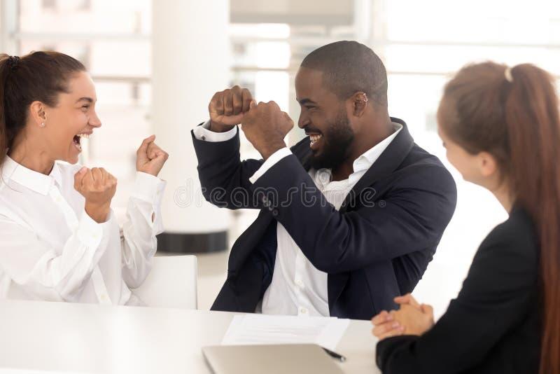 Diverse millennial werknemers die bij werkplaats startsucces vieren stock afbeeldingen