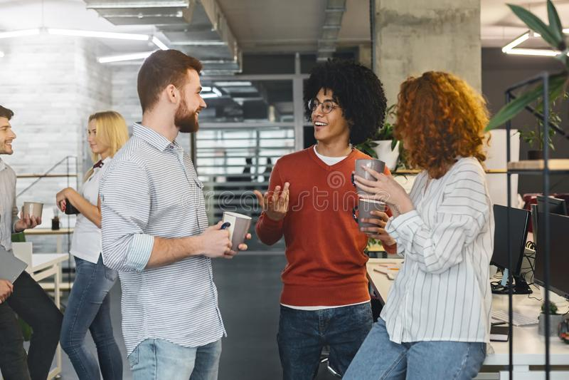 Diverse millennials die van mededeling in modern bureau genieten stock fotografie
