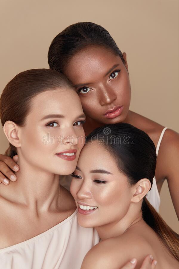 Free Diverse. Models Beauty Portrait. Ethnic Women With Nude Makeup And Glowing Skin Standing Together Against Beige Background. Stock Photos - 187879943