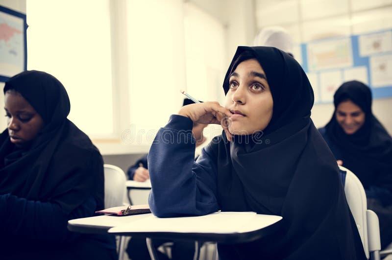 Diverse Moslimkinderen die in klaslokaal bestuderen stock fotografie