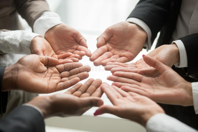 Diverse multi-ethnic business team members join hands together p. Diverse multi-ethnic business team members join helping hands group together palms up as royalty free stock image