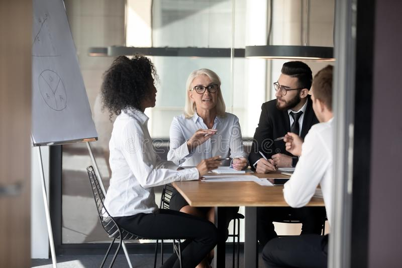Diverse multiethnic colleagues talk brainstorming at office meeting stock image