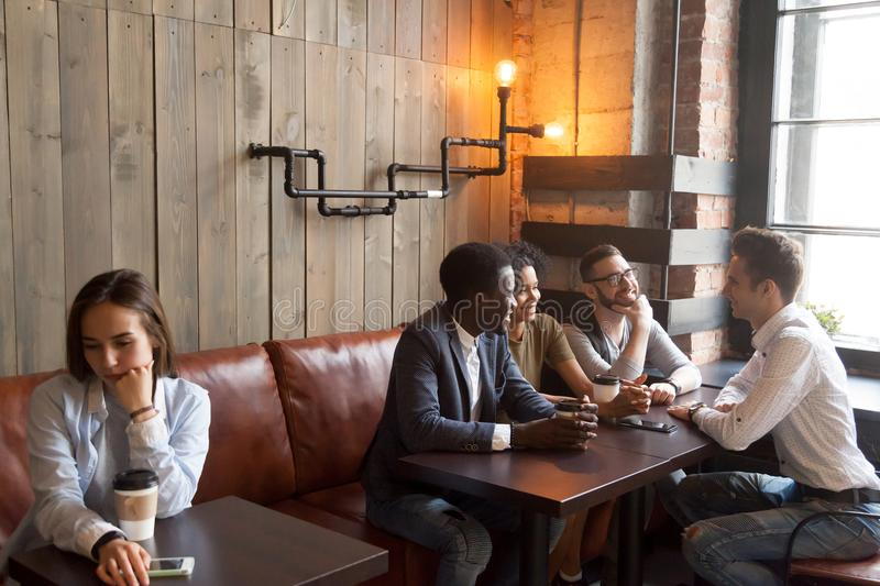 Diverse young friends ignoring sad girl sitting alone in cafe stock photos