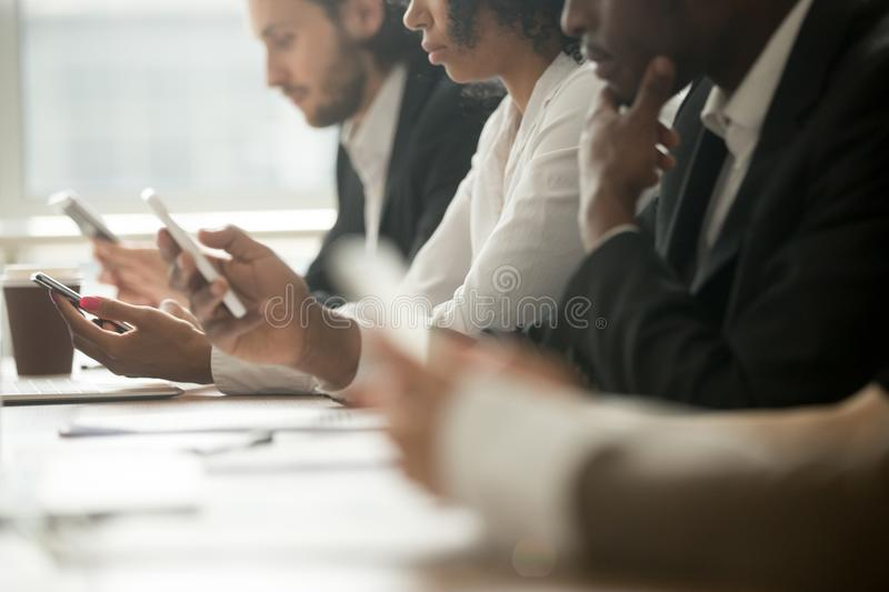 Diverse business people holding using mobile phones, close up vi stock photo