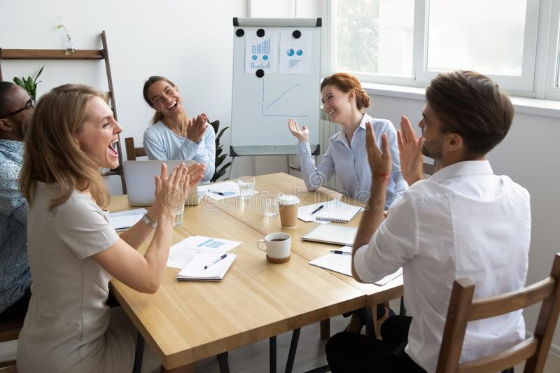 Diverse office workers team laughing and applauding at funny joke. At corporate group business meeting. Excited smiling multiracial employees chatting, having royalty free stock photos