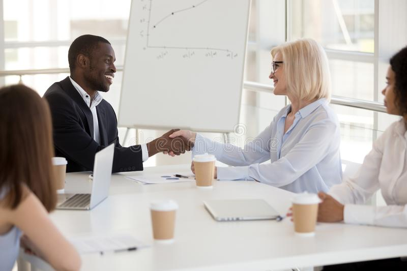 Diverse partners shaking hands at business meeting, respect conc. Friendly young african american businessman and smiling mature caucasian businesswoman shaking stock photo