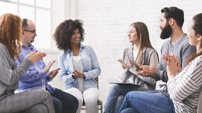 Diverse people applauding to themselves at therapy session in rehab royalty free stock images