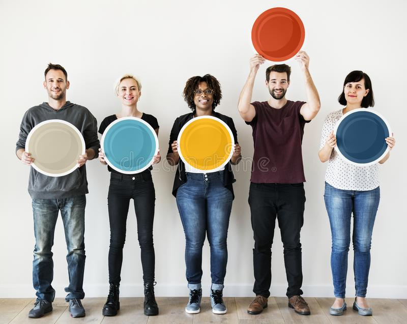 Diverse people holding blank round board stock photo