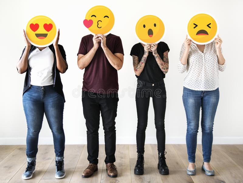 Diverse people holding emoji icons stock photography