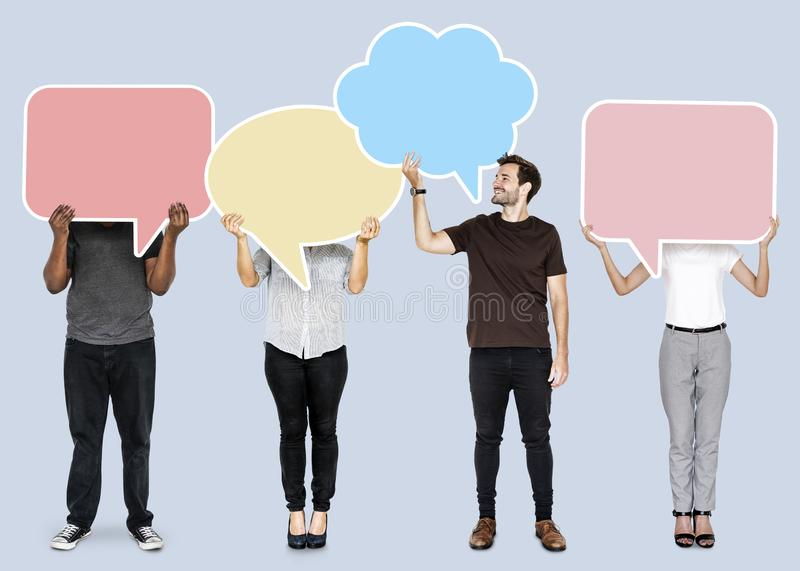 Diverse people holding empty speech bubbles stock photo