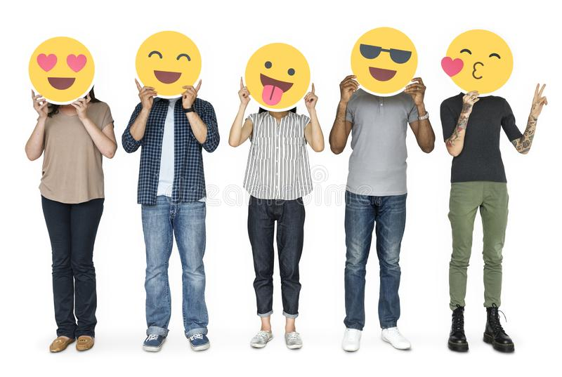 Diverse people holding happy emoticons stock photos