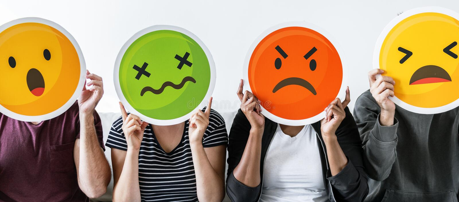 Diverse people holding various emoticons royalty free stock photo