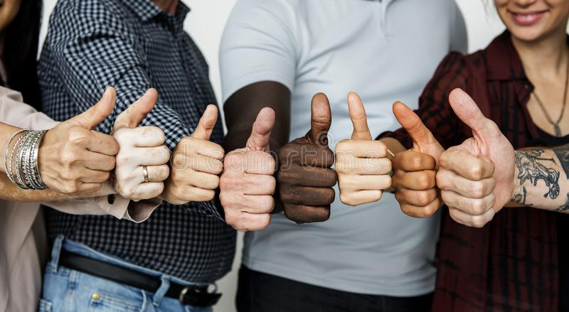 Diverse people showing up thumbs stock photos