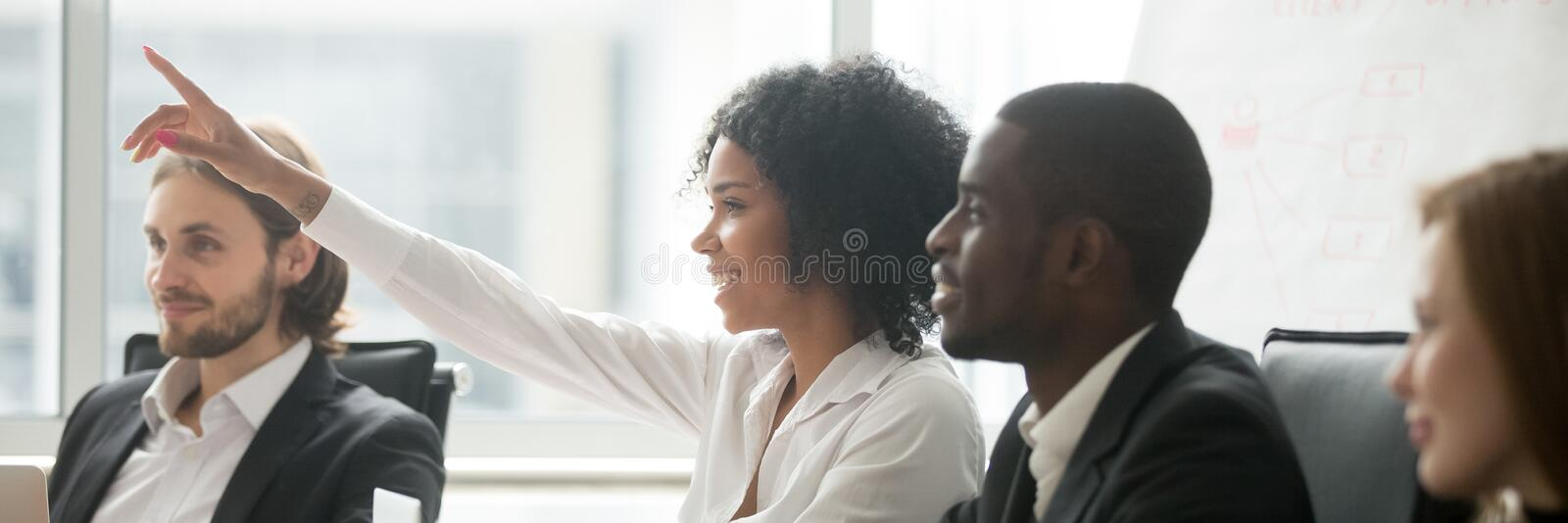 African woman raise hand ask question during seminar at boardroom royalty free stock photos