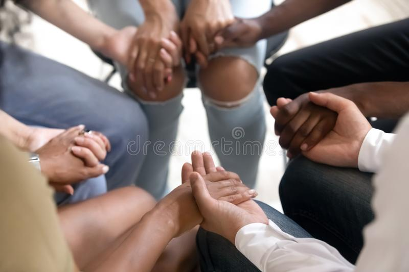 Diverse people sitting in circle holding hands at group therapy. Session, religious christian team pray together for recovery give psychological support stock photography