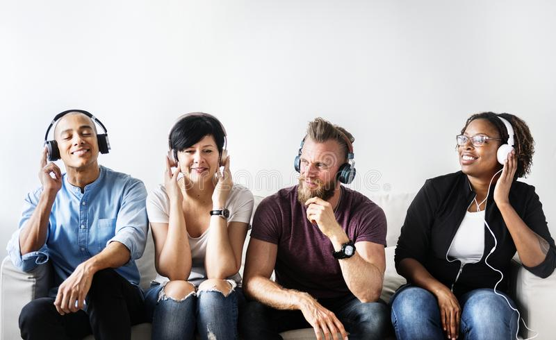 Diverse people sitting on the couch wearing headphones royalty free stock photography