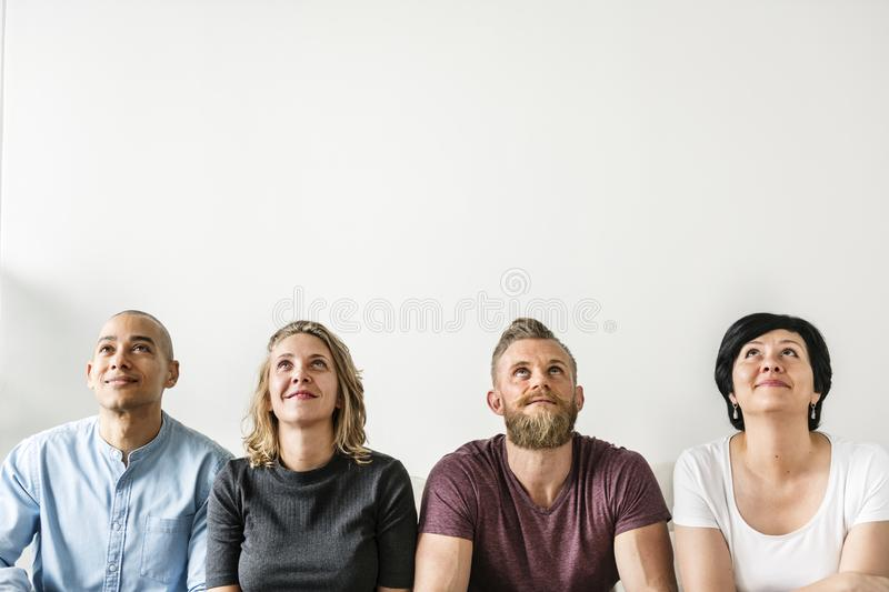 Diverse people sitting with thoughtful face expression royalty free stock image